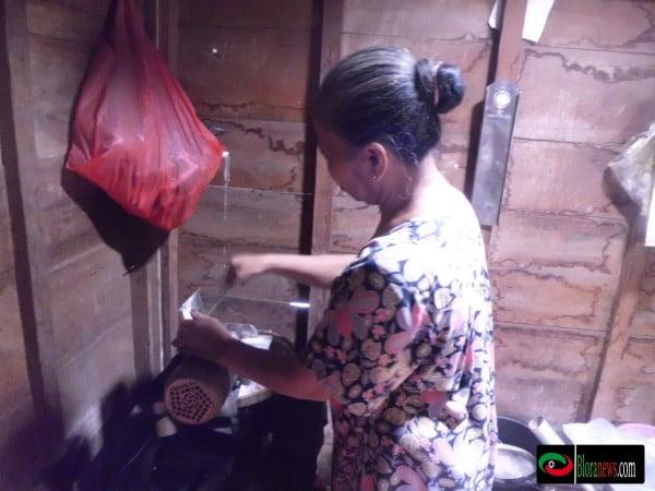 Ibu Rukmini sang pemilik warung sedang meracik kopi santan