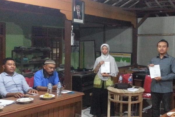 Dua Calon Kades PAW Desa Bogorejo menunjukkan nomor undian di depan peserta Musdes