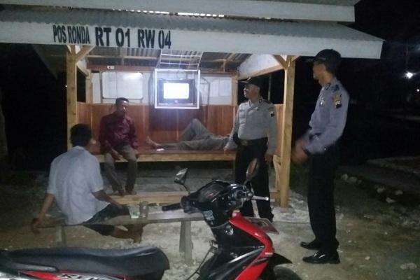 Petugas menyambangi warga yang sedang berjaga di Poskamling