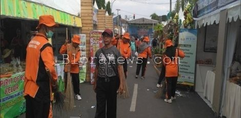 Pasukan Sapu Jagad atau Tim Oranye tengah beraksi membersihkan sampah bekas acara Pameran HPS 2018