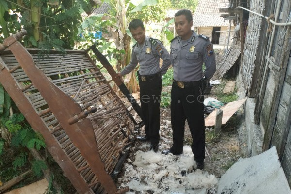 Petugas Polsek Ngawen menunjukkan kasur yang terbakar, diduga akibat puntung rokok yang menyala