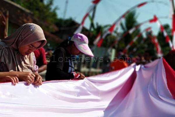 Ibu-ibu di Desa Karangtengah Kecamatan Ngawen Kabupaten Blora menjahit bendera merah putih secara manual dengan tangan