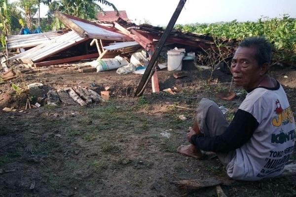 Seorang lansia menyaksikan rumahnya roboh akibat terjangan angin kencang