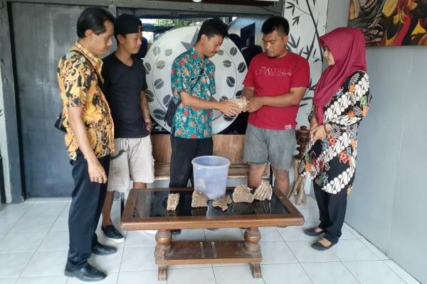 Kasi Sejarah dan Kepurbakalaan Dinporabudpar Blora Eka Wahyu Hidayat (batik hijau) menerima fragmen fosil Gajah Purba dari penemu, Susana (kaos merah)