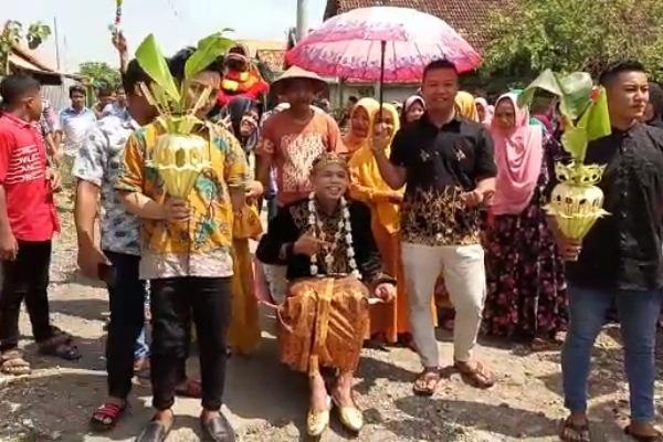 Mempelai pria, M Rokhim diantar menuju rumah mempelai wanita dengan menaiki angkong (gerobak dorong)