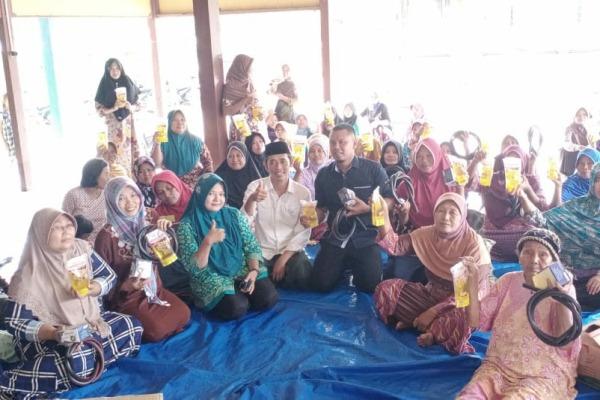 Kepala Desa Sempu, Lilik Zubaidi (peci hitam) membagikan minyak goreng gratis kepada warga setempat