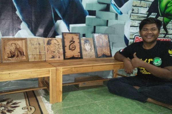 M Fahrurrozi bersama lukisan pirografi buatannya