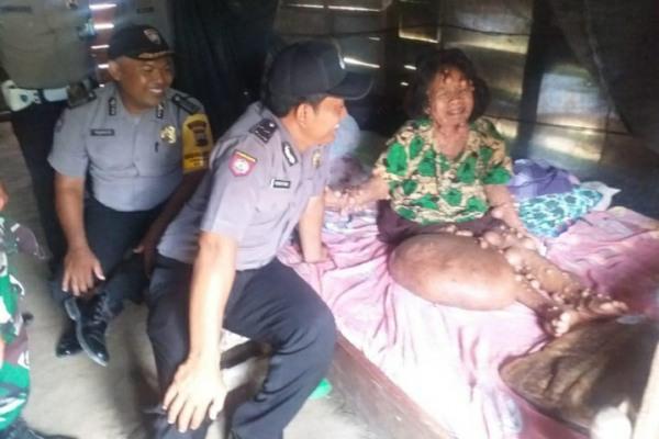 Petugas Polsek Jati Polres Blora menyerahkan bantuan kepada Lasiyem