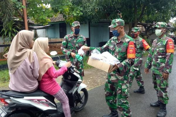 Anggota Koramil Ngawe membagikan Masker untuk pengguna jalan yang melintas didepan mako koramil Ngawen