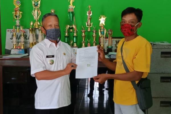 Imam Syafi'i (Baju Kuning) Menyerahkan Surat Pernyataan Pengembalian Bantuan Sosial Tunai Kepada Kepala Desa Brumbung, Supardi.